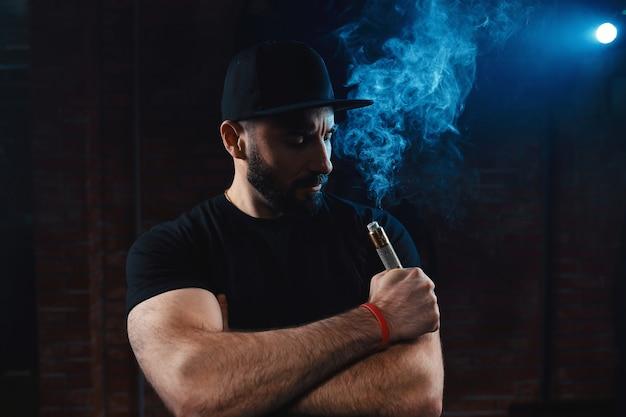 Mann, der eine elektronische zigarette vaping ist