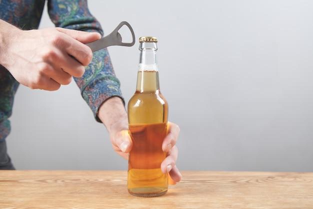 Mann, der eine flasche bier auf dem holztisch öffnet.