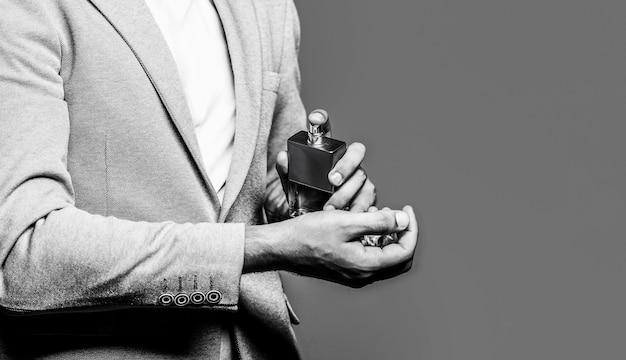 Mann, der eine flasche parfüm hält. männerparfüm in der hand auf anzughintergrund. mann im anzug, flasche parfüm, nahaufnahme. duftgeruch. fashion köln flasche. platz kopieren. platz kopieren.