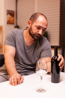 Mann, der eine flasche rotwein hält, enttäuscht wegen untreuer frau