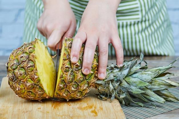 Mann, der eine frische ananas auf einem hölzernen schneidebrett schneidet
