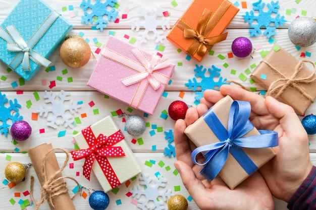 Mann, der eine geschenkbox auf den weihnachtsdekorationen hält