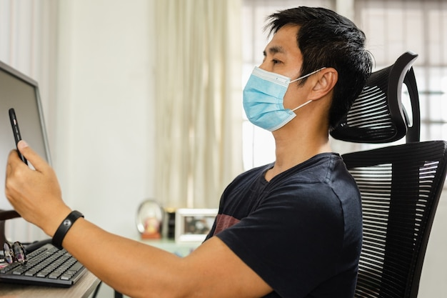 Mann, der eine gesichtsmaske trägt, während von zu hause aus gearbeitet wird