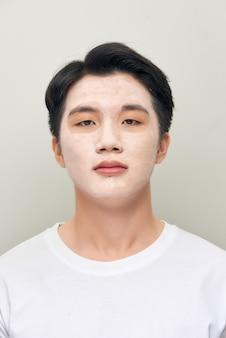 Mann, der eine gesichtsmasken-schönheitsbehandlung anwendet