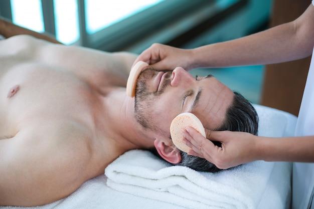 Mann, der eine gesichtsmassage vom masseur empfängt