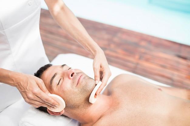 Mann, der eine gesichtsmassage vom masseur im badekurort empfängt