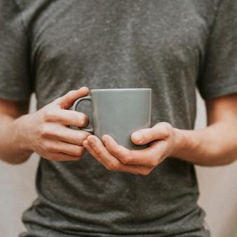 Mann, der eine graue keramische kaffeetasse hält