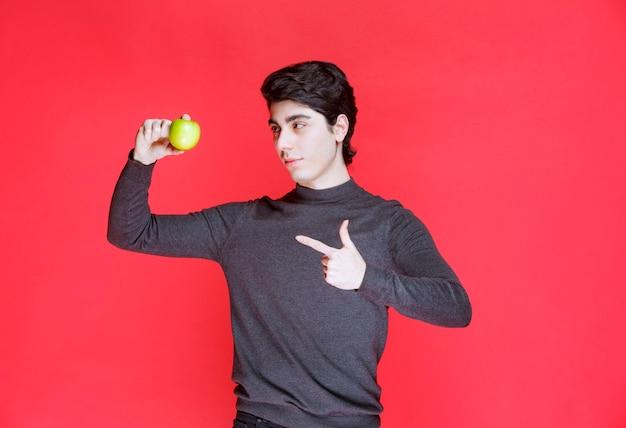 Mann, der eine grüne mandarine hält und darauf zeigt