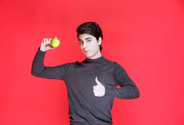 Mann, der eine grüne mandarine hält und es genießt