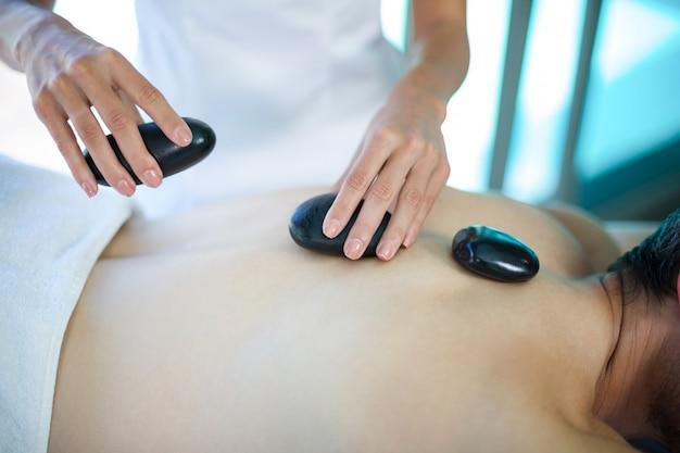 Mann, der eine heiße steinmassage vom masseur empfängt