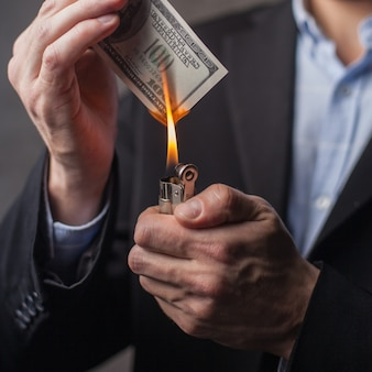 Mann, der eine hundert-dollar-note brennt. nahaufnahme