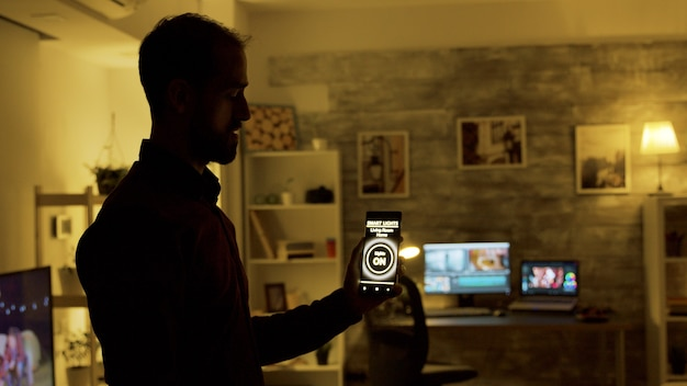 Mann, der eine intelligente lichtanwendung verwendet, um die glühbirnen im haus einzuschalten.