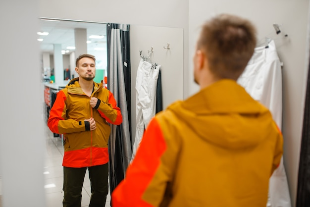 Mann, der eine jacke für ski oder snowboarden, sportgeschäft anprobiert.