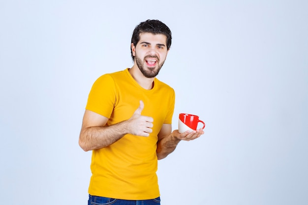 Mann, der eine kaffeetasse hält und den geschmack genießt.