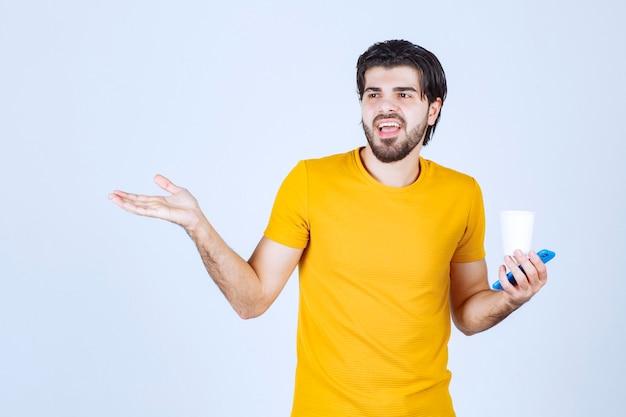 Mann, der eine kaffeetasse hält und präsentation mit offener hand hält.