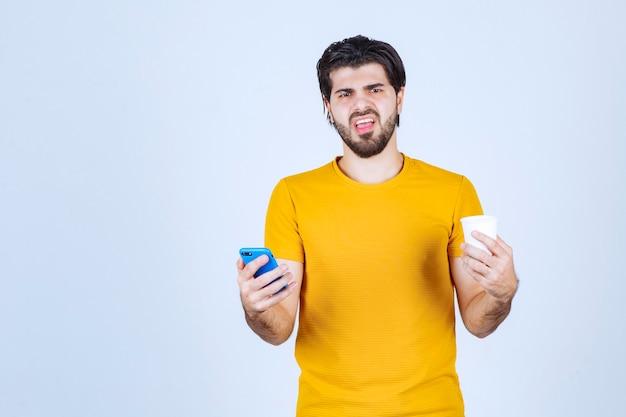 Mann, der eine kaffeetasse hält und sein neues modell-smartphone vorführt.