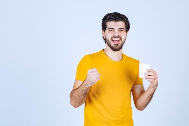 Mann, der eine kaffeetasse hält und seine macht zeigt.