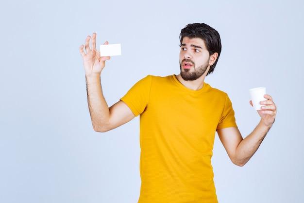 Mann, der eine kaffeetasse hält und seine visitenkarte vorlegt.