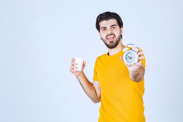 Mann, der eine kaffeetasse und einen wecker hält, der auf die morgenroutine zeigt.