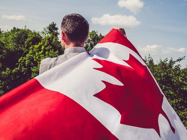 Mann, der eine kanadische flagge wellenartig bewegt. nationalfeiertag