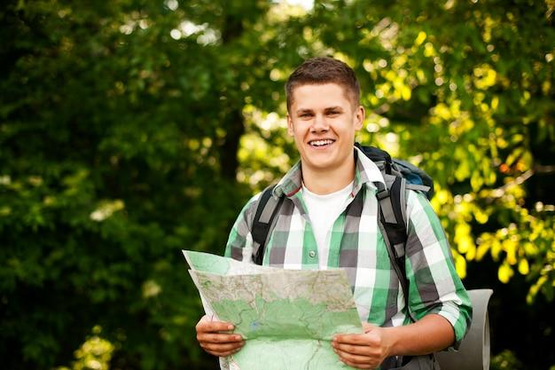 Mann, der eine karte im wald hält