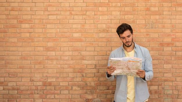 Mann, der eine karte mit kopienraum betrachtet