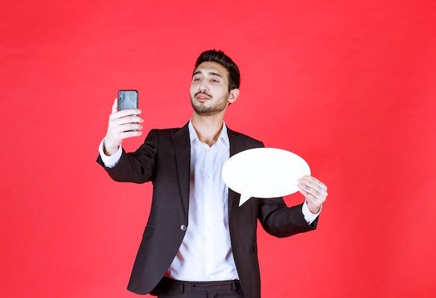 Mann, der eine leere ovale infotafel hält und mit dem telefon spricht oder einen videoanruf tätigt.