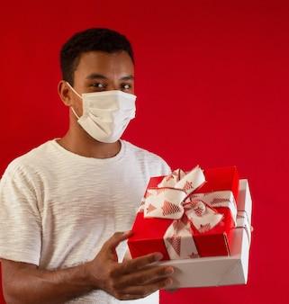 Mann, der eine maske mit geschenk in seinen händen trägt