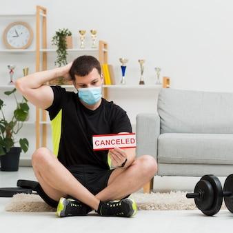 Mann, der eine medizinische maske trägt, während sportbekleidung zu hause trägt