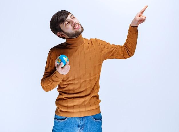 Mann, der eine minimalistische weltkugel hält