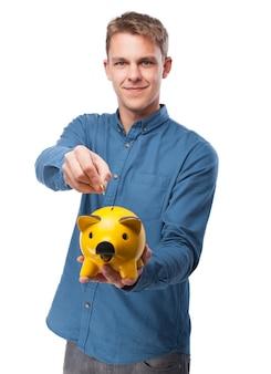 Mann, der eine münze in ein gelbes schwein sparschwein gießen