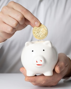 Mann, der eine münze in ein sparschwein einführt