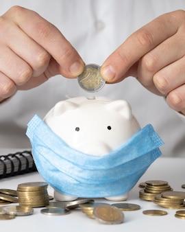 Mann, der eine münze in ein sparschwein mit einer medizinischen maske einführt