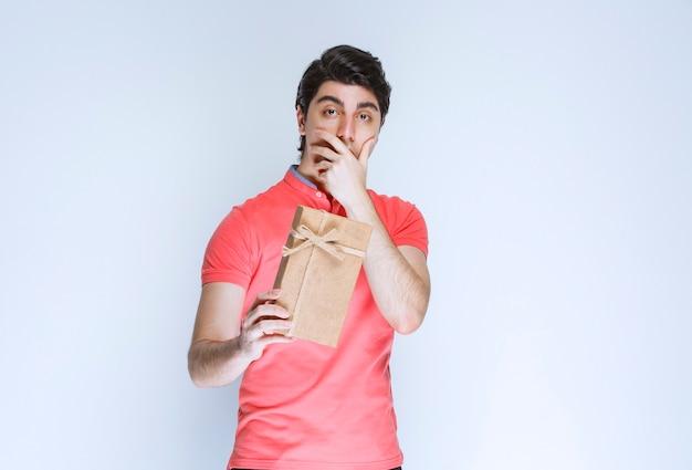 Mann, der eine pappgeschenkbox mit überraschung hält.