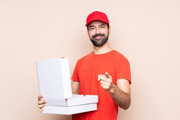 Mann, der eine pizza über lokalisierter wand hält