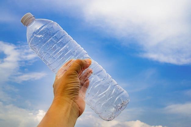 Mann, der eine plastikflasche wasser hält