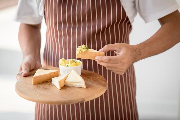 Mann, der eine platte von toast mit honig und käse hält