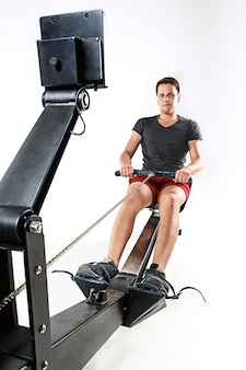 Mann, der eine pressmaschine in einem fitness-club verwendet.