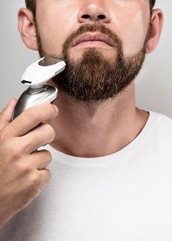 Mann, der eine rasiermaschine benutzt