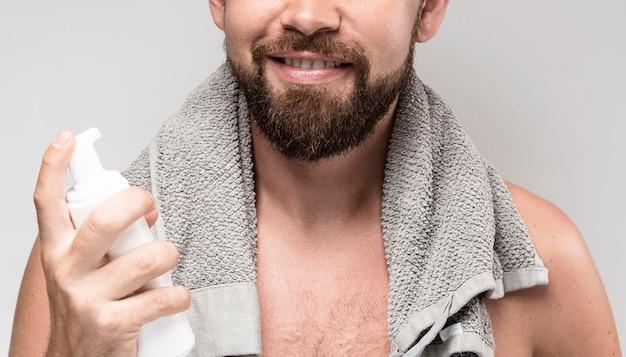 Mann, der eine rasierschaumflasche hält