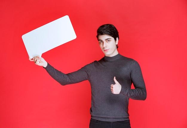 Mann, der eine rechteckige ideentafel hält und positives handzeichen zeigt