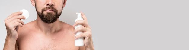 Mann, der eine reinigungsscheibe und rasierschaumflasche hält