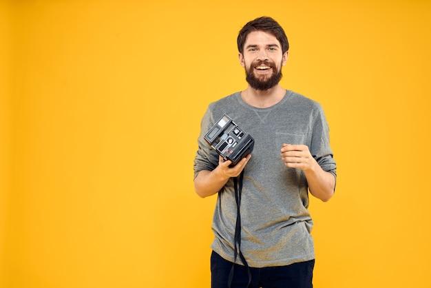 Mann, der eine retro-fotokamera auf gelbem hintergrund verwendet