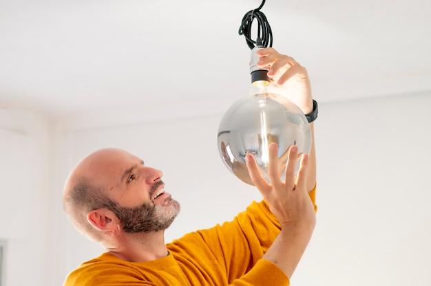 Mann, der eine riesige moderne glühbirne platziert
