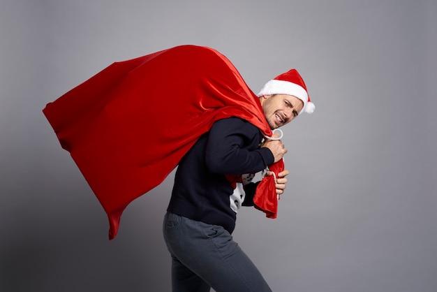 Mann, der eine riesige tasche voller weihnachtsgeschenke trägt