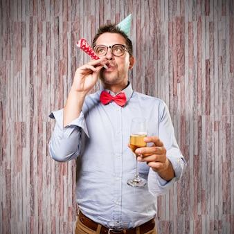 Mann, der eine rote fliege und partei-hut trägt. halten sie einen champagner gla