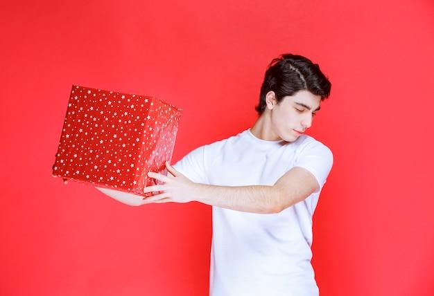 Mann, der eine rote geschenkbox am valentinstag anbietet