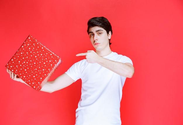 Mann, der eine rote geschenkbox hält und darauf zeigt