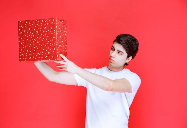 Mann, der eine rote geschenkbox hält und sie prüft