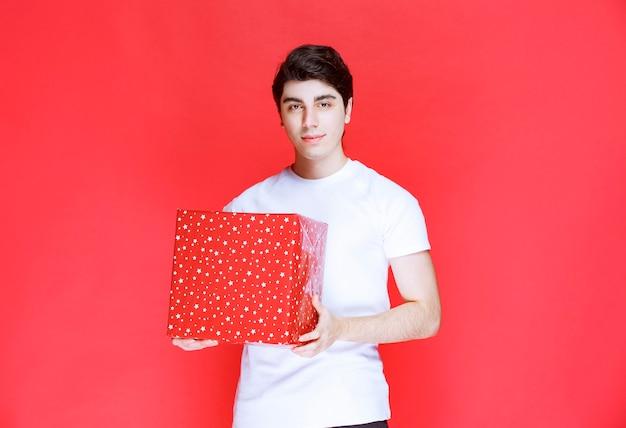 Mann, der eine rote große geschenkbox hält